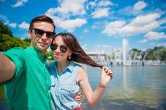 Pares turísticos jovenes que viajan el días de fiesta en la sonrisa de Europa feliz Muchacha caucásica y hombre que hacen el fond Imagen de archivo libre de regalías
