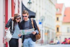 Pares turísticos jovenes que viajan en la sonrisa de los días de fiesta al aire libre feliz Familia caucásica con el mapa de la c Fotografía de archivo libre de regalías