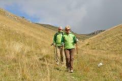 Pares turísticos mayores que caminan en las montañas hermosas fotos de archivo