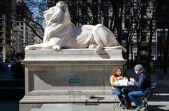 Pares turísticos que desayunan en los pasos de la biblioteca pública de Nueva York Fotos de archivo