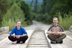 Pares turísticos que se sientan en un puente de madera Imagenes de archivo