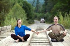 Pares turísticos que se sientan en un puente de madera y que llevan a cabo las manos Imagen de archivo
