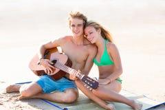 Pares turísticos rubios que tocan la guitarra en la playa Imagenes de archivo