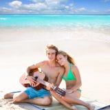 Pares turísticos rubios que tocan la guitarra en la playa Fotografía de archivo libre de regalías