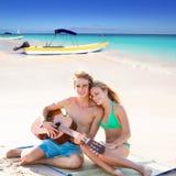 Pares turísticos rubios que tocan la guitarra en la playa Fotografía de archivo