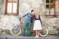 Pares tur?sticos jovenes, hombre hermoso y mujer bastante rubia montando la bicicleta en t?ndem a lo largo de la calle de la ciud fotografía de archivo