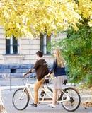 Pares tur?sticos jovenes, hombre hermoso y mujer bastante rubia montando la bicicleta en t?ndem a lo largo de la calle de la ciud foto de archivo libre de regalías