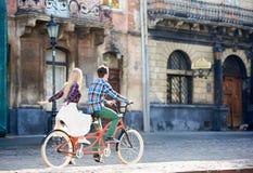 Pares tur?sticos jovenes, hombre hermoso y mujer bastante rubia montando la bicicleta en t?ndem a lo largo de la calle de la ciud foto de archivo
