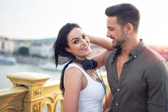 Pares urbanos jovenes felices con los auriculares en el aire libre fotografía de archivo
