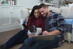 Pares usando el ordenador portátil con su perro casero en sala de estar foto de archivo