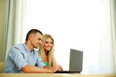 Pares usando el ordenador portátil junto en casa Foto de archivo libre de regalías