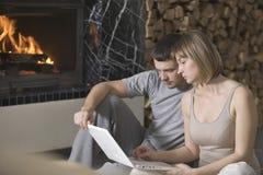 Pares usando el ordenador portátil mientras que se sienta por la chimenea en la casa Imagen de archivo libre de regalías
