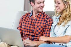 Pares usando el ordenador portátil en el sofá Imagen de archivo libre de regalías