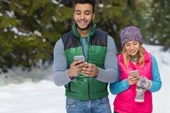 Pares usando el teléfono elegante que charla invierno al aire libre que camina de la nieve de la mujer en línea de Forest Happy S Fotografía de archivo libre de regalías