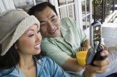 Pares usando el teléfono móvil en el pórtico Foto de archivo libre de regalías