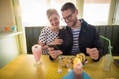Pares usando el teléfono móvil en restaurante Foto de archivo