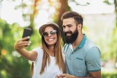 Pares usando el teléfono móvil que toma un selfie en el parque fotos de archivo libres de regalías