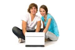 Pares usando la computadora portátil Imágenes de archivo libres de regalías