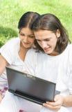 Pares usando la computadora portátil, al aire libre Imagen de archivo