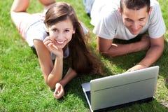 Pares usando la computadora portátil al aire libre Imagen de archivo libre de regalías