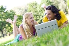 Pares usando la computadora portátil al aire libre Fotos de archivo libres de regalías
