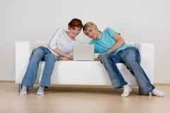Pares usando la computadora portátil en el sofá Fotografía de archivo libre de regalías