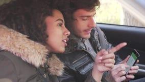 Pares usando la navegación en el teléfono móvil durante viaje por carretera del coche almacen de metraje de vídeo