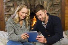 Pares usando la tableta delante de la chimenea encendida Fotografía de archivo libre de regalías