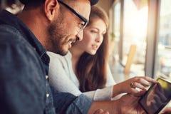 Pares usando la tableta digital en el café Foto de archivo libre de regalías