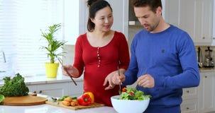 Pares usando la tableta digital mientras que prepara la ensalada en la cocina 4k almacen de video