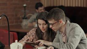 Pares usando la tableta digital y cachimba que fuma en el café de Shisha Fotografía de archivo