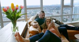 Pares usando la tableta digital y el teléfono móvil en la sala de estar 4k almacen de video