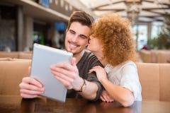 Pares usando la tableta en restaurante Imagen de archivo libre de regalías