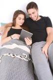 Pares usando la tablilla en cama Imagen de archivo libre de regalías