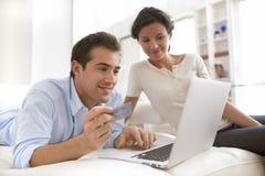Pares usando la tarjeta de crédito a hacer compras en línea Fotografía de archivo libre de regalías