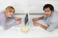 Pares usando las computadoras portátiles Foto de archivo libre de regalías