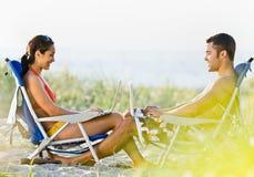 Pares usando las computadoras portátiles en la playa Foto de archivo libre de regalías