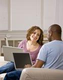 Pares usando las computadoras portátiles en sala de estar Foto de archivo libre de regalías