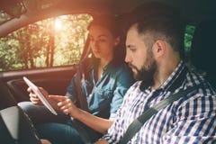 Pares usando los gps en el compter de la tableta a navegar en coche el día de fiesta Fotografía de archivo libre de regalías