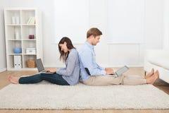 Pares usando los ordenadores portátiles en sala de estar Foto de archivo libre de regalías