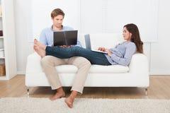 Pares usando los ordenadores portátiles en el sofá Imagenes de archivo