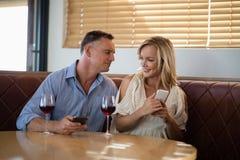Pares usando los teléfonos móviles mientras que comiendo el vidrio de vino Foto de archivo