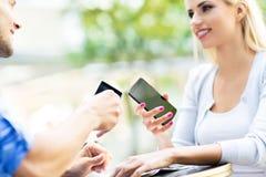 Pares usando los teléfonos móviles para compartir ficheros Fotografía de archivo