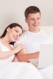 Pares usando o computador junto na cama Imagens de Stock