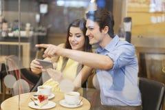 Pares usando o móbil Imagens de Stock Royalty Free