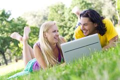 Pares usando o portátil ao ar livre Fotos de Stock Royalty Free