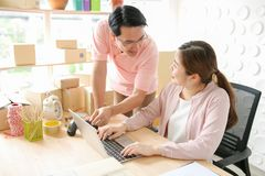 Pares usando o portátil em casa Apontar na tela com felizmente SME, ordem do produto da verificação, vendendo em linha, comércio  fotos de stock