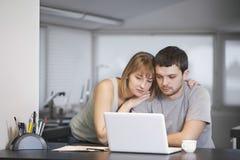 Pares usando o portátil junto no contador de cozinha Imagens de Stock