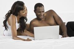 Pares usando o portátil na cama fotos de stock royalty free