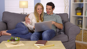 Pares usando o portátil no sofá Imagens de Stock Royalty Free